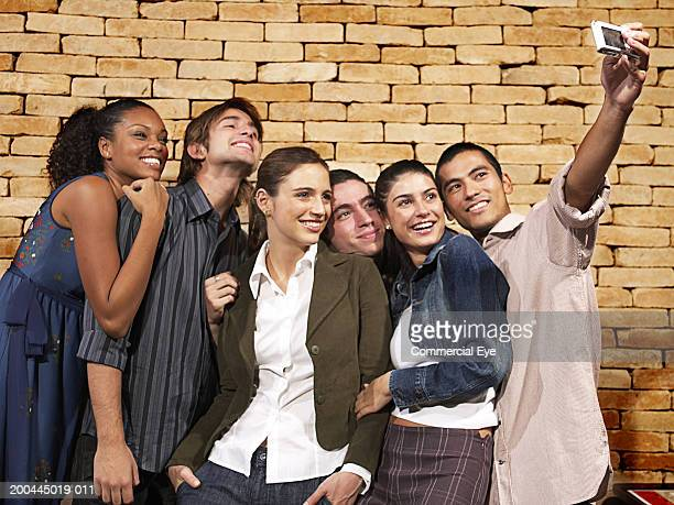 Young people taking group portrait with camera phone