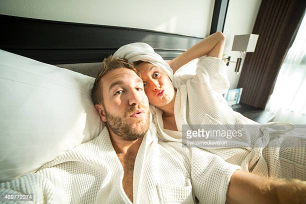 Young people taking selfie in bed