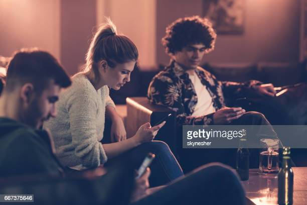 Young people text messaging on cell phones in a cafe.