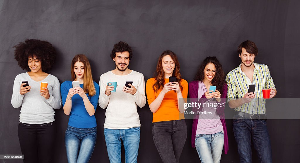 Young people text messaging : Stock Photo