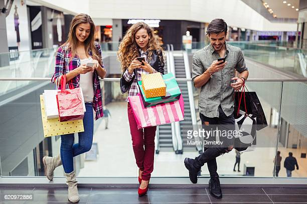 Young people texting in the shopping center