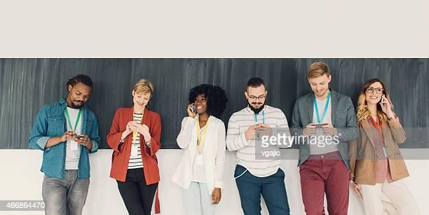 Junge Menschen Tippen und Gespräch auf ihren Smartphones.