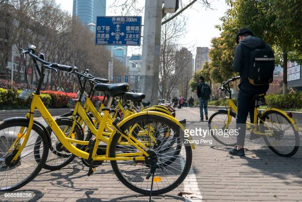 Young people unlocks a share bike with an app on his mobile phone 'Dockless' share bikes have flooded on the streets of Chinese cities Besides Mobike...