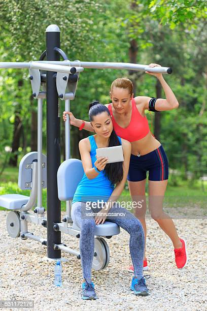 young people using a digital tablet in the park - belly ring stock photos and pictures