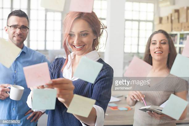 Young people using adhesive notes at work
