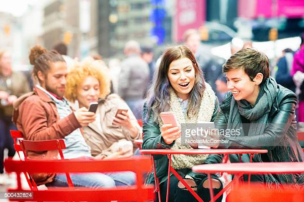 Young people using phones sitting in Times Square
