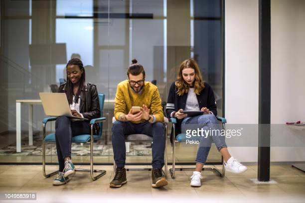 young people using technology in waiting room - man bun stock pictures, royalty-free photos & images