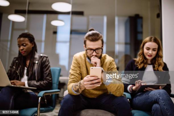 Young people using technology in waiting room