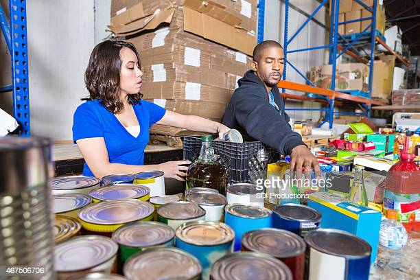 young people volunteering to sort donations for charity food drive - food bank stock pictures, royalty-free photos & images