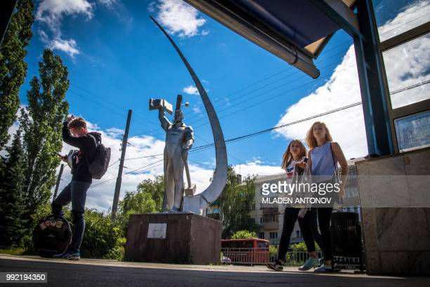 Young people walk in front of a Soviet era monument in Nizhny Novgorod on July 5 2018 Nizhny Novgorod stadium will host the quarterfinal football...