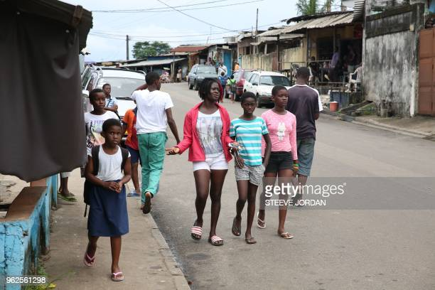 Young people walk in the street of the popular district of Kinguele in Libreville on May 24 2018 The tolibangando slang used in the popular districts...