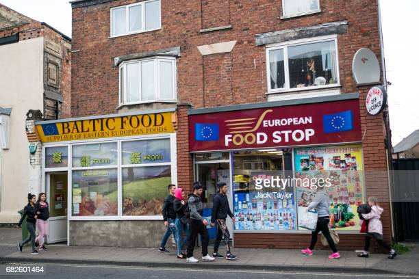 Young people walk past two European food markets on May 12 2017 in Boston United Kingdom The town of Boston in Lincolnshire voted with a 75% majority...