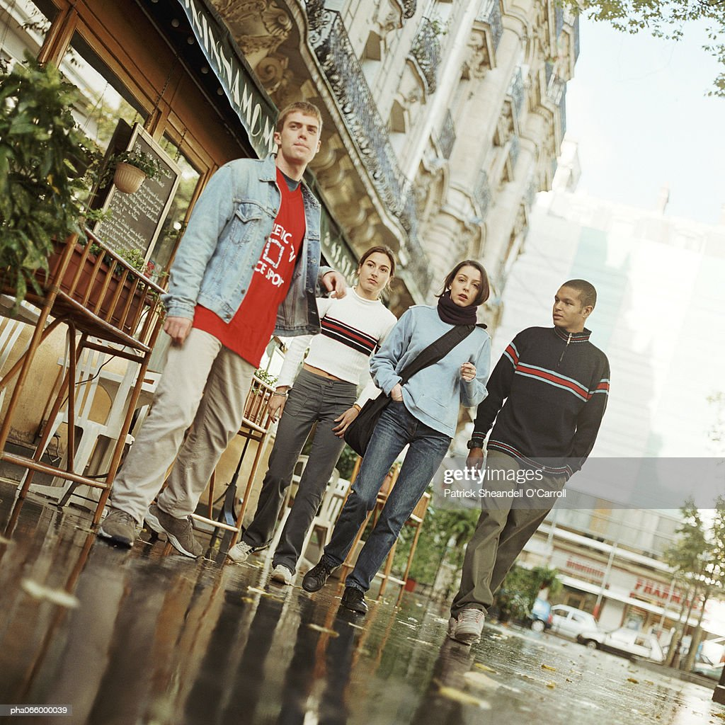 Young people walking together outside near cafe, full length : Stockfoto