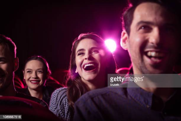 young people watching comedy movie in the cinema - humour stock pictures, royalty-free photos & images