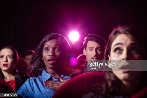 young people watching thriller movie in the cinema - scary movie stock photos and pictures