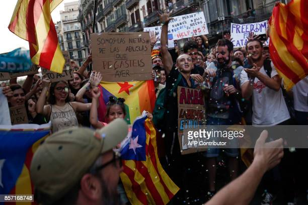 """Young people wave Catalan pro-independence 'Estelada' flags and a placard reading """"We are the granddaughters of the grandmothers you beat yesterday""""..."""