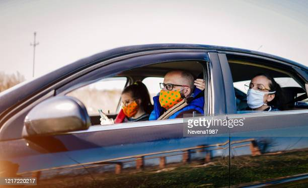 covid-19, young people wearing disposable face mask while driving - car interior stock pictures, royalty-free photos & images