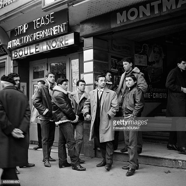Young people wearing leather jackets waiting in front of a cinema and the Cabaret 'La Boule Noire' on the boulevard de Rochechouart in November 1961...