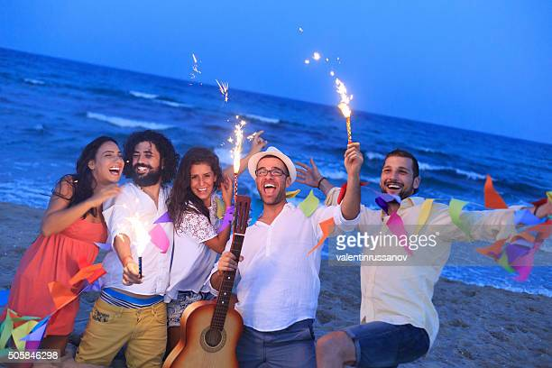 Young people with fireworks on the beach