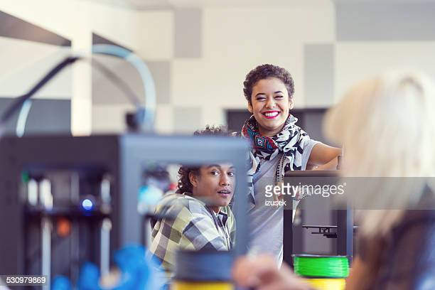 Young people working in 3D printer office