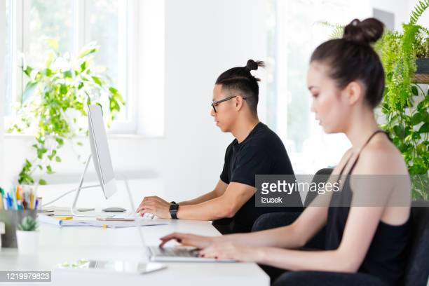 young people working in the creative workplace - shirt stock pictures, royalty-free photos & images