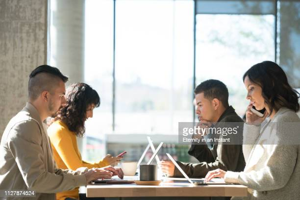 young people working on laptops in a cafe - hot desking stock pictures, royalty-free photos & images