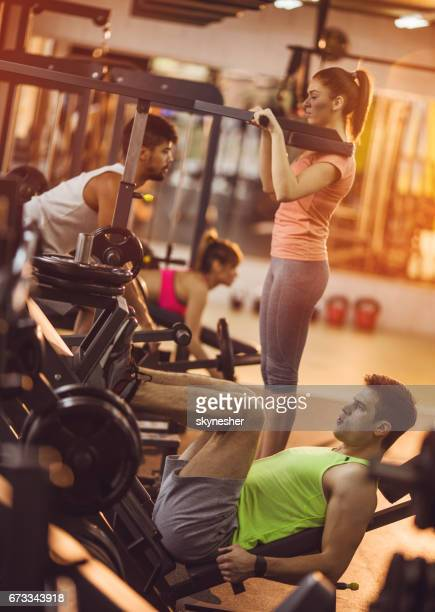 Young people working out on exercise machines in a gym.