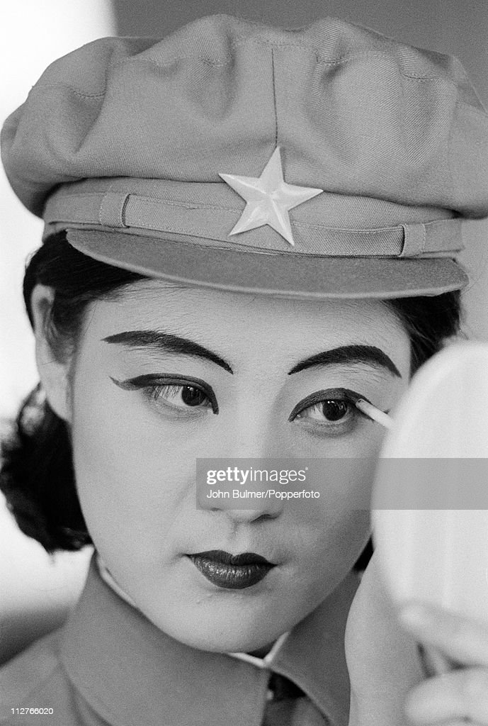 A young woman in uniform applying eye-liner, North Korea, February 1973.