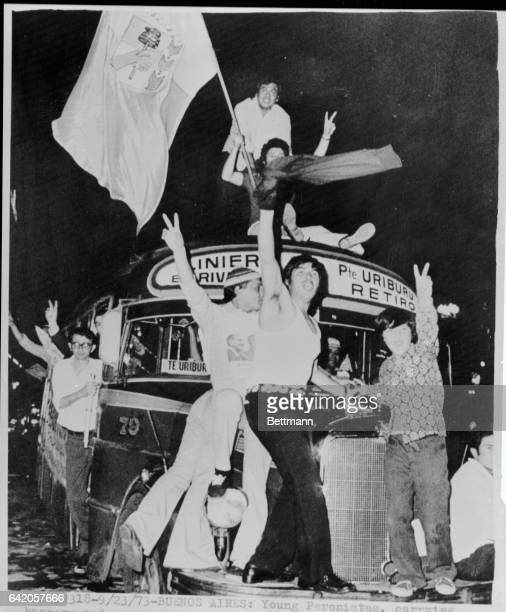 Young Peronistas carrying banners and posters have taken over a bus on Plaza de Mayo during joyful spontaneous demostration marking Juan D Peron's...