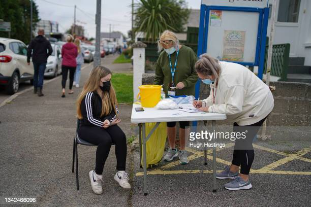 Young person being interviewed before receiving a Pfizer Covid vaccination at an NHS walk-up vaccination unit outside the village hall on September...