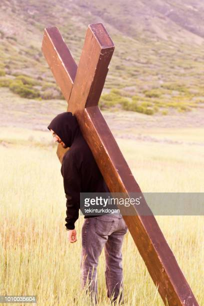 young person carrying christian cross on shoulder at santaquin valley of salt lake city slc utah usa - spanish fork utah stock pictures, royalty-free photos & images