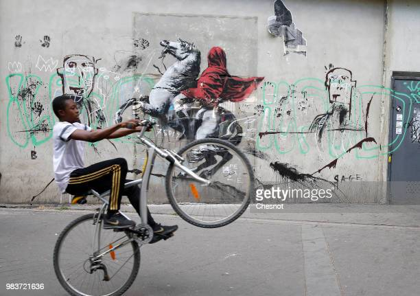 A young person goes by his bike in front of a recent artwork attributed to street artist Banksy on June 25 2018 in Paris France Six frescoes...