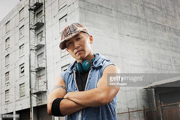 a young person in a denim sleeveless shirt, arms folded looking at the camera.  - sleeveless stock pictures, royalty-free photos & images