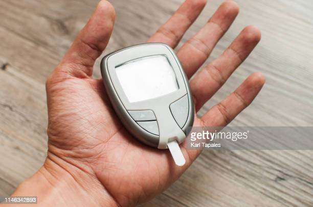 a young person is holding a device for determining the blood glucose level - glycemia stock pictures, royalty-free photos & images