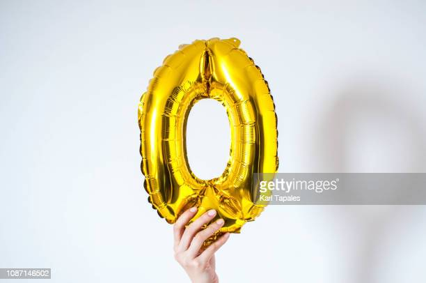a young person is holding a golden-colored number zero on a white background - letra o - fotografias e filmes do acervo