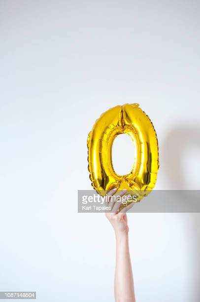A young person is holding a golden-colored number zero on a white background