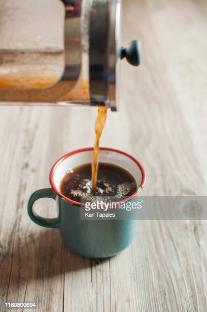 a young person is pouring freshly brewed coffee from a french press to a coffee cup - daily life in philippines stock pictures, royalty-free photos & images