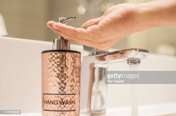 A young person is using a hand wash liquid soap