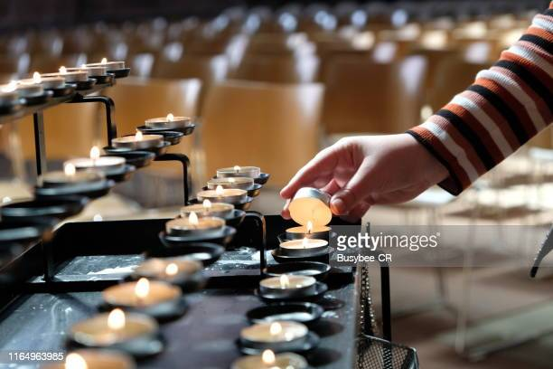 a young person lighting a candle in a cathedral - candle of hope stock pictures, royalty-free photos & images