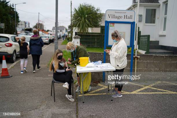 Young person receives a Pfizer Covid vaccination at an NHS walk-up vaccination unit outside the village hall on September 25, 2021 in the village of...