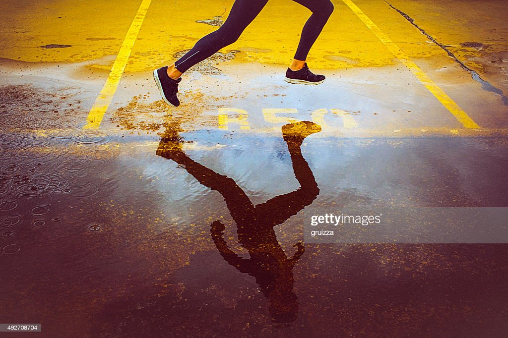 Young person running over the parking lot : Stock Photo