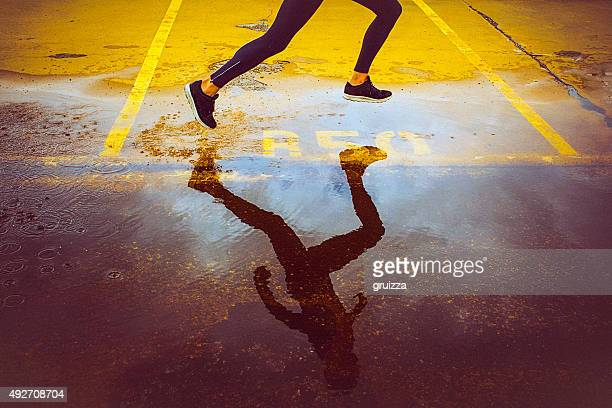 young person running over the parking lot - schaduw stockfoto's en -beelden