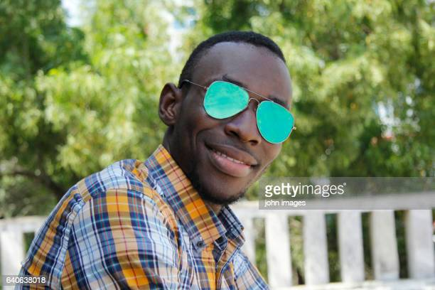 a young person smiling with his glasses - personne humaine stock-fotos und bilder
