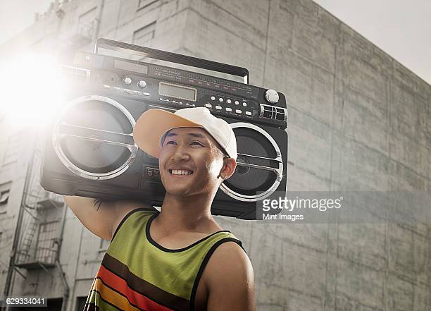 A young person with a boombox on the street of a city.