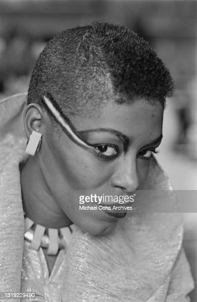 Young person with heavy eye make-up, a close-cropped hairstyle, with matching earrings and necklace, location unspecified, January 1981.