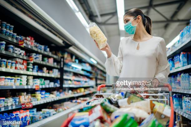 young person with protective face mask buying groceries/supplies in the supermarket.preparation for a pandemic quarantine due to coronavirus covid-19 outbreak.choosing nonperishable food essentials - consumentisme stockfoto's en -beelden
