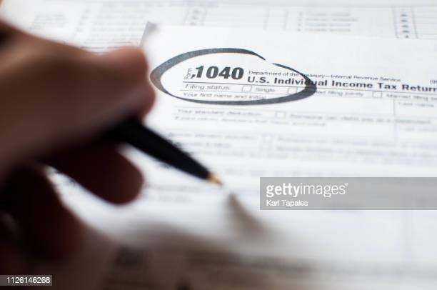 a young person writing on a tax document - tax stock pictures, royalty-free photos & images