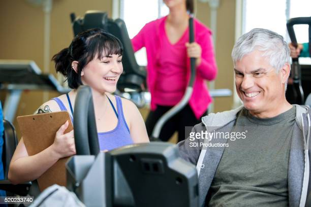 Young personal trainer helping senior male client