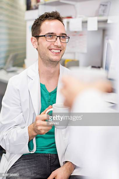 Young pharmacist having coffee break