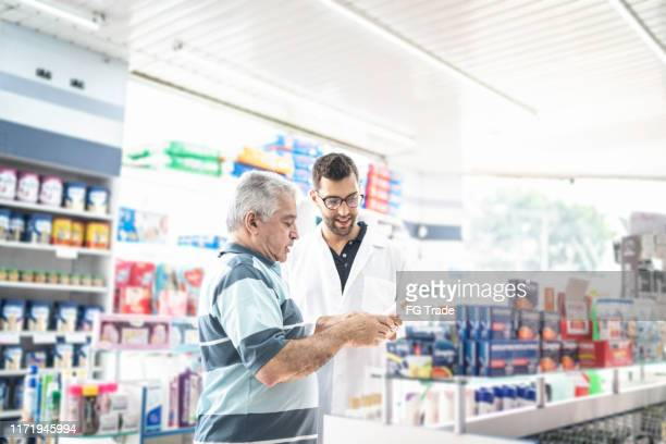 young pharmacist helping a customer finding a medicine - pharmacy stock pictures, royalty-free photos & images